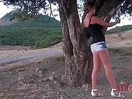 Suntanned girl with pretty face walked down the hill then leisurely undressed by tree 5
