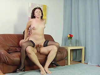 Red-haired mature in sexy outfit was relaxing alone on couch when young fellow joined her