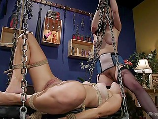 Tied up brunette licked mistress' pussy before strapon intruded into her asshole