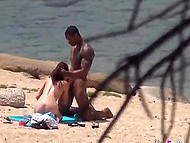 Red-haired chick bends over black guy, who massages her back and puts cock in pussy on beach 10