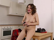 Mature woman in leather gloves made herself comfortable on table and rubbed bushy pussy 7