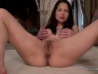Asian MILF with tight body has fun at fireplace and spreads her pussy lips right on camera