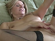 Mature lady in fishnet stockings and high heels actively masturbates an unshaven vagina