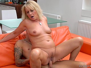 Tattooed youngster actively uses his hard penis to satisfy mature lady on orange sofa