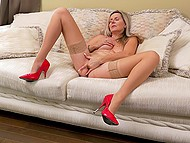 Mature lady in stockings and red shoes sat on sofa and stuck mischievous fingers into pussy