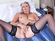 Raunchy female in black stockings gently kneads her trimmed pussy with fingers