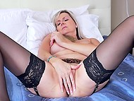 Raunchy female in black stockings gently kneads her trimmed pussy with fingers 9