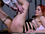 Dominant woman bites submissive chick with electricity and spanks her booty in various ways