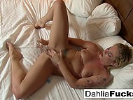 Tattooed blonde polishes clitoris and thrusts dildo into smooth pussy bringing herself heavenly delight