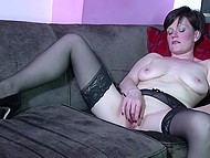 Hot MILF in sexy lingerie adores playing with her charming pussy on couch