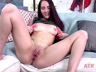 Elegant brunette slowly removes clothes gently stimulating trimmed vagina on white couch