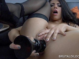 Brunette in black stockings is almost crying in pleasure when huge dildos hammer tight asshole