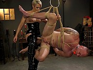 Dominant blonde in latex fucks hanged man with strapon then saddles his cock with pussy