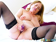 Mature blonde is touching her nipples to arouse herself before pushing hot fingers into pierced pussy