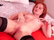 Red-haired MILF with small tits touches her body and shoves finger into divine hole
