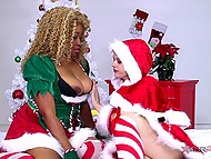 Sexy elf punishes her black friend by slapping her tight ass while Santa is busy with his affairs
