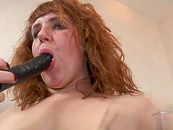 Red-haired BBW with hypnotizing saggy boobs plays with her hairy cunt using black dildo