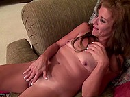 Mature lady with tanned body lies on couch and stimulates her shaved vagina with vibrator 5