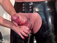 Two mistresses in latex suits handle tied up male's erect cock to make him cum in femdom video 10