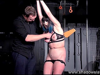 Man spanks mature woman's ass with paddle and attaches clothespins to pierced nipple