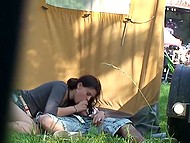 Perverted guy hides in tent and films young couple fucking on green grass at rock festival