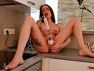 Busty chick climbs on kitchen countertop to masturbate pussy with powerful vibrator and piss 6