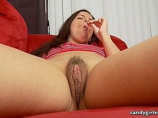 Long-haired woman likes to expose her trimmed vagina as well as sucking caramel candies