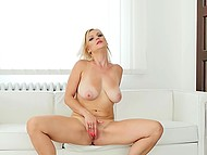 Sexy cougar with natural breasts tenderly rubs shaved pussy alone on white couch