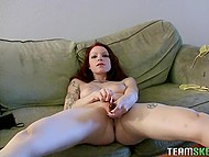 Skinny cutie with long red hair and perky tits toys her shaved peach alone on couch