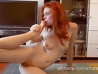 Kinky redhead with flexible body takes off underwear and licks manicured fingers on feet