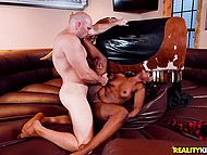 Ebony girl receives pleasure from riding on mechanical bull and bald man's cock inside cunt