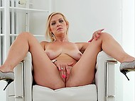 Experienced blonde with juicy natural breasts gently rubs shaved pussy in armchair 4