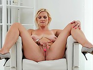 Experienced blonde with juicy natural breasts gently rubs shaved pussy in armchair 5