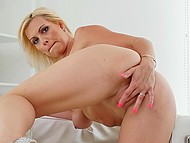 Experienced blonde with juicy natural breasts gently rubs shaved pussy in armchair 9