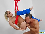 Inventive Marsha May hangs on red bed sheet and athletic man fucks blonde's pussy