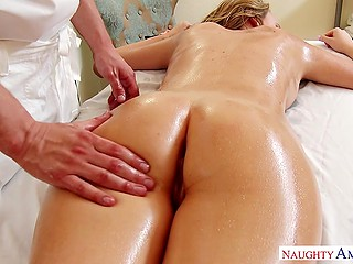 Hot blonde lies on table and experiences awesome massage given by talented rubber