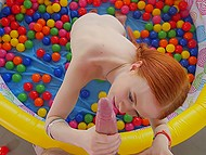 Teen redhead with long braids gives boyfriend blowjob being in pool with marbles and he licks her anus