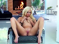 Enticing blonde with natural curves gladly shows shaved pussy alone in living room