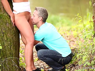 Gray-haired man pays some compliments to beautiful hottie and licks her pussy on lake