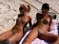 Clip with participation of two naked girls sunbathing on beach and splashing in azure seawater