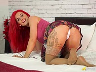 Fiery-red temptress lifts up her skirt to demonstrate smooth pussy and round buttocks 6