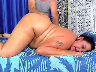 Old master massages back of fat brunette client and caresses her vagina with vibrator