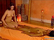Tender hands of naked masseuse with red hair bring to enjoyable Indian girl a lot of pleasure