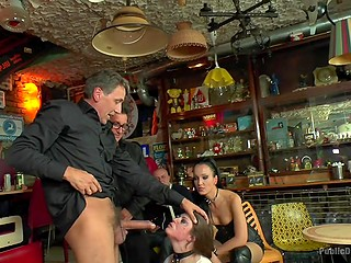 Obedient slut is dominated by two masters and their assistant in bar full of usual people