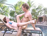 Couple of young lovers has passionate sex right by the summer pool on deck chair 4