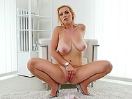 Experienced blonde with juicy boobs sits on armchair and gently touches her peach