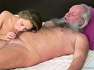 Grey-haired old man lies on the bed trying to find an occupation and young wife comes to be fucked 4