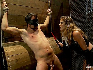 Merciless mistress in leather outfit uses tazapper to hurt tied up man who is blindfolded and wears chastity belt