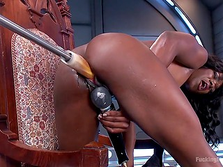 Fuck-machine penetrates into the wet pussy of black chick at high speed while she is stimulating clitoris with vibrator