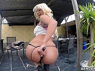 Blonde lady with impressive butt cheeks comes outdoors to test some new sex toys
